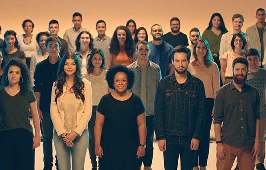 Image with Itaú employees standing on an orange background.
