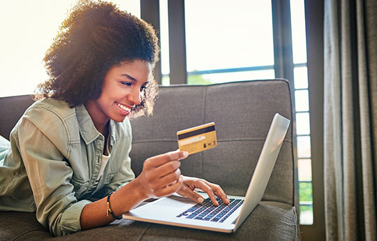 Smiling girl lying on couch with credit card in hand and fiddling with notebook.