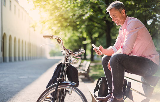 Smiling man sitting on a bench in a square, fiddling with his cell phone and his bicycle parked in front of him.