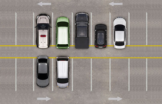 Aerial image of a parking lot with seven parked cars.